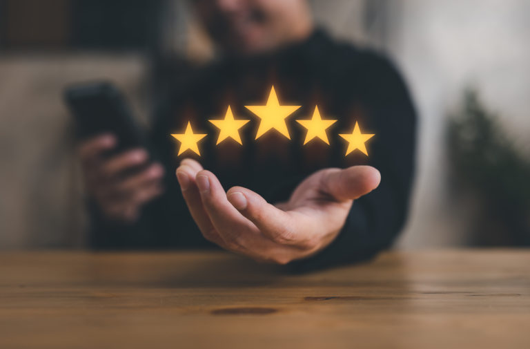 hand of customer or client holding the stars to complete five stars. with copy space. giving a five star rating. Service rating, satisfaction concept.
